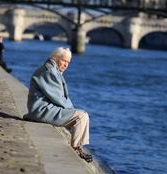 Old woman sitting on Seine's riverbank